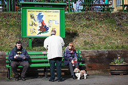 © Licensed to London News Pictures. 07/03/2014. Hampshire, UK. People waiting in the sunshine at Ropley Station today, 7th March 2014, which is the first day of the 'spring steam gala' on the Watercress Line. The railway line, operated by Mid Hants Railway Ltd, passes between Alresford and Alton in Hampshire. The line is named after its use in the past for transporting freshly cut watercress from the beds surrounding Alresford to London. Photo credit : Rob Arnold/LNP