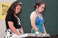 Mercedes Cokeley (left) and Megan Brinker perform during the 8th grade recognition ceremony at Cleveland PK-8 School in Dayton, May 25, 2012.