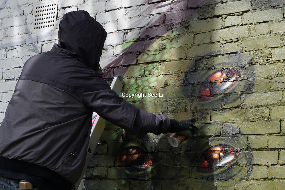 London,England,UK : 10th April 2016 : Fiya One street artists paint a live orangutan for the 'Endangered 13' at Ackroyd Drive Sponsor by Tower Hamlets council in London. Photo by See Li
