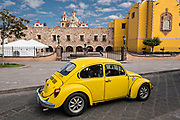 A yellow Volkswagen battle passes the Aranzazu Chapel and San Francisco Convent in the Plaza de Aranzazu in the state capital of San Luis Potosi, Mexico. The chapel and convent was built between 1749 and 1760 and features Churrigueresque details and tiled domes.