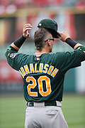 ANAHEIM, CA - JULY 21:  Josh Donaldson #20 of the Oakland Athletics dons his cap during the game against the Los Angeles Angels of Anaheim on Sunday, July 21, 2013 at Angel Stadium in Anaheim, California. The Athletics won the game in a 6-0 shutout. (Photo by Paul Spinelli/MLB Photos via Getty Images) *** Local Caption *** Josh Donaldson