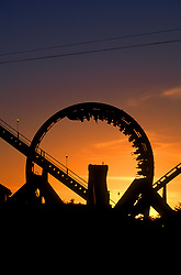 Stock photo of a roller coaster going through a loop at sunset at AstroWorld in Houston Texas