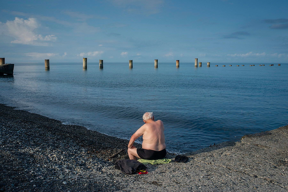 A man sits on a towel on a beach. In the background a construction project, which was destroyed in the war between Abkhazia and Georgia in 1992 - 1993, is visible. Ochamchira, Abhkazia