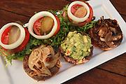 Three mini hamburgers with onions, guacamole and mushrooms