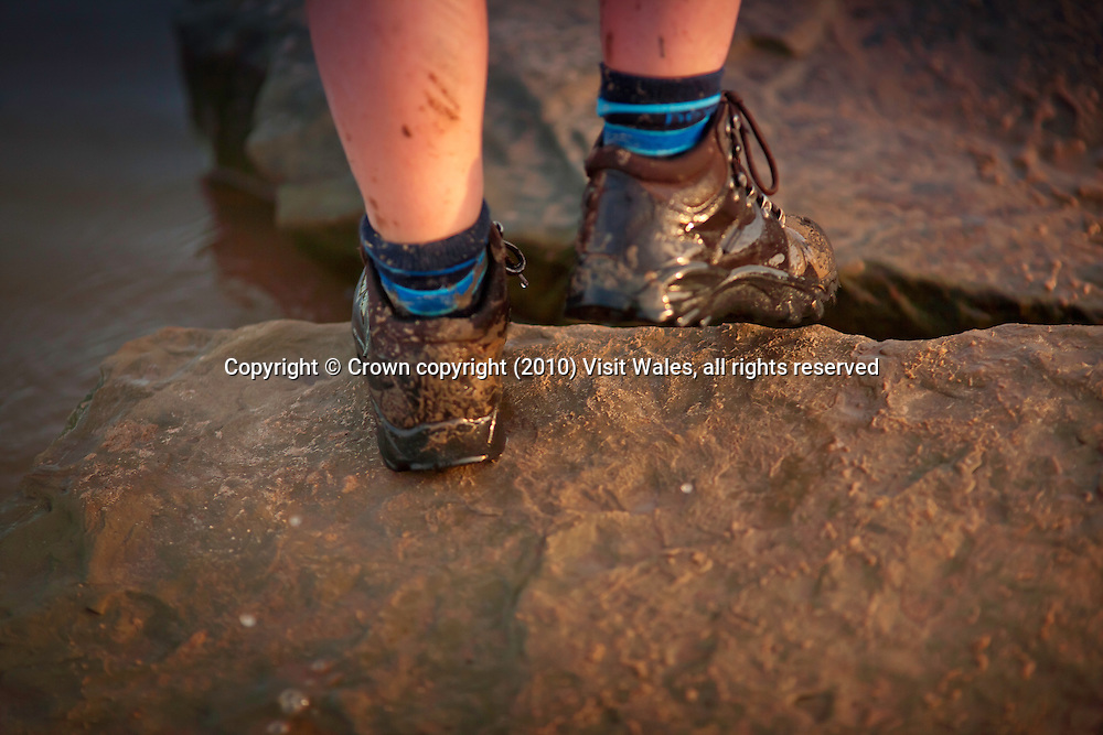 Close-up of young boy's feet splashed with mud<br /> Walking<br /> Wales Coast Path<br /> Near Point of Ayr<br /> Flintshire<br /> North<br /> Activities and Sports