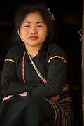Khmu tribal woman of Ban Nalantai village in traditional wear inside her bamboo thatched hut