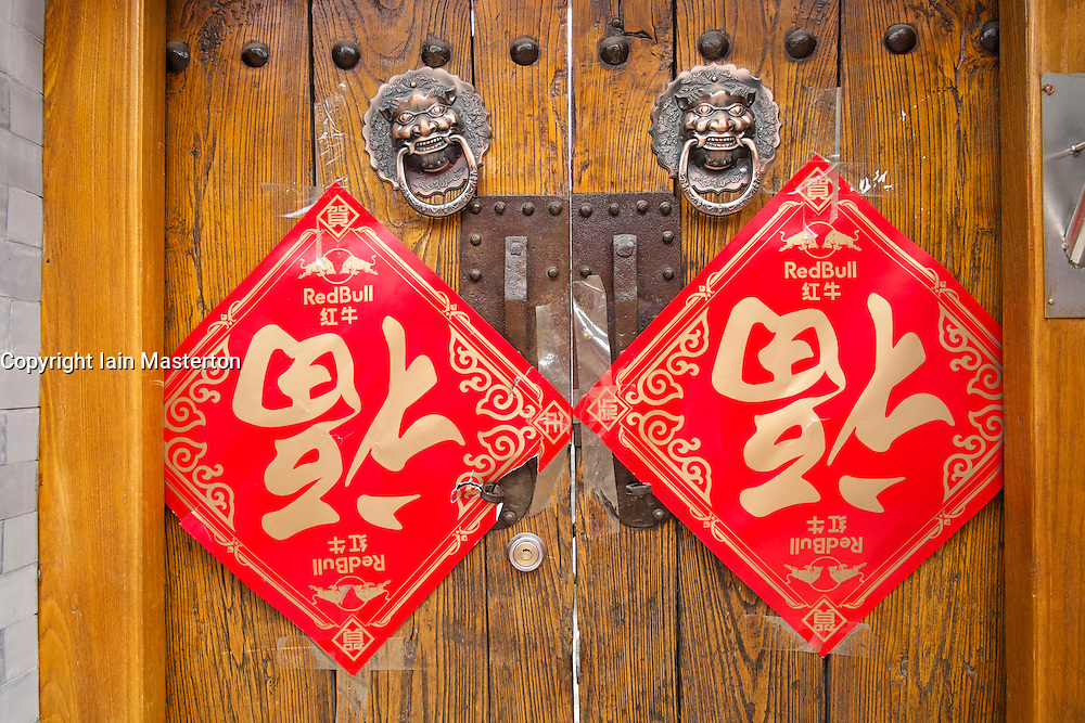 Old wooden doors at entrance to traditional courtyard house in a Beijing hutong or lane in China