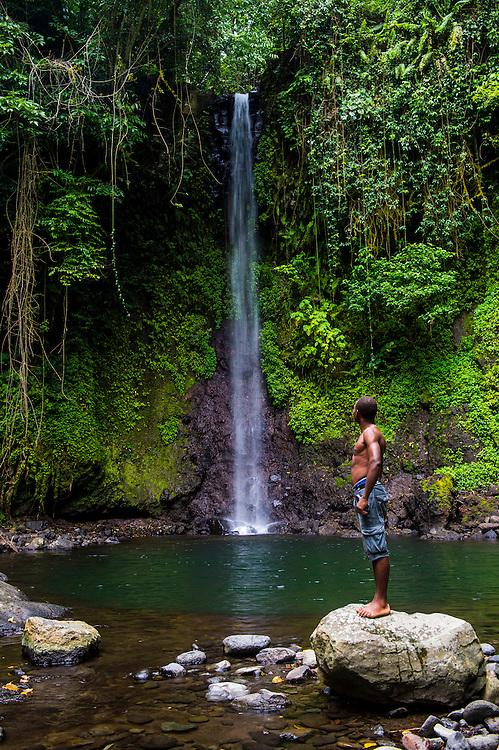 Einheimischer an einem Wasserfall inmitten des Dschungels