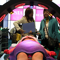 "BEIJING, 22. October 2004 : a model lies in a ""slimming machine ""at the International Beauty Week in Beijing, October 22, 2004, in China. Beauty business is booming in China. Sales in beauty related businesses and products are worth more than 7 billion USD last year.      ..Whereas in Mao Zedong's China, even pigtails were seen as a sign of vanity (and had to be cut off) , nowadays, urban Chinese women seek about every means in order to distinguish themselves from the masses.  This year Beijing will organize the worl'd first beauty pageant for women had had plastic surgery in early December..."