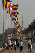 "30 JANUARY 2013 - PHNOM PENH, CAMBODIA:   People walk along Sisowath Quay in Phnom Penh where flags at half mast for late Cambodian King Norodom Sihanouk. Sihanouk (31 October 1922 - 15 October 2012) was the King of Cambodia from 1941 to 1955 and again from 1993 to 2004. He was the effective ruler of Cambodia from 1953 to 1970. After his second abdication in 2004, he was given the honorific of ""The King-Father of Cambodia."" Sihanouk held so many positions since 1941 that the Guinness Book of World Records identifies him as the politician who has served the world's greatest variety of political offices. These included two terms as king, two as sovereign prince, one as president, two as prime minister, as well as numerous positions as leader of various governments-in-exile. He served as puppet head of state for the Khmer Rouge government in 1975-1976. Most of these positions were only honorific, including the last position as constitutional king of Cambodia. Sihanouk's actual period of effective rule over Cambodia was from 9 November 1953, when Cambodia gained its independence from France, until 18 March 1970, when General Lon Nol and the National Assembly deposed him. Upon his final abdication, the Cambodian throne council appointed Norodom Sihamoni, one of Sihanouk's sons, as the new king. Sihanouk died in Beijing, China, where he was receiving medical care, on Oct. 15, 2012. His cremation is scheduled to take place on Feb. 4, 2013. Over a million people are expected to attend the service.        PHOTO BY JACK KURTZ"