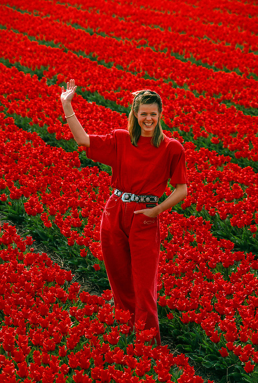 Dutch woman standing in flower bulb field near Lisse, the Netherlands