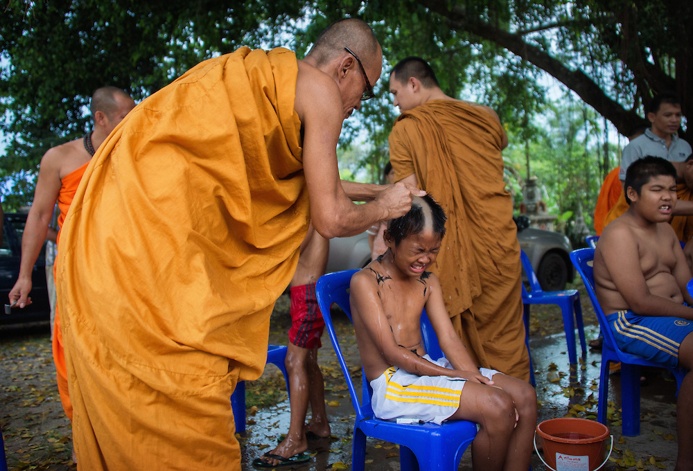 Young men endure the pain of having their heads shaved as they prepare to become novice monks in  rural Nakhon Nayok, Thailand.