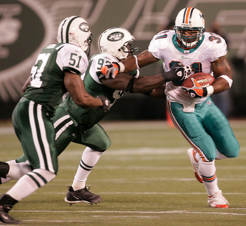 Miami Dolphins running back Sammy Morris (R) runs upfield past the New York Jets Defense of Jonathan Vilma (R) Shaun Ellis (center) in the first  quarter of their game at Giants Stadium in East Rutherford New Jersey Monday 01 November 2004.  EPA/ANDREW GOMBERT