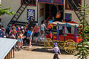 Young people visit the Theatre Royal, built in 1868, in Barkerville Historic Town & Park, British Columbia, Canada. Historically the main town of the Cariboo Gold Rush, Barkerville is now the largest living-history museum in Western North America. The town was named after Billy Barker from Cambridgeshire, England, who struck gold here in 1861, and his claim became the richest and the most famous. This National Historic Site nestles in the Cariboo Mountains at elevation 1200m (4000ft), at the end of BC Highway 26, 80 kilometres (50 mi) east of Quesnel. Gold here was first discovered at Hills Bar in 1858, followed by other strikes in 1859 and 1860. Wide publication of these discoveries in 1861 began the Cariboo Gold Rush, which reached full swing by 1865 following strikes along Williams Creek.