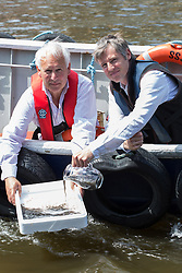 Zac Goldsmith MP (R) and Andrew Kerr (L) Chairman of Sustainable Eel Group, release several thousands of eels from a boat into the Thames in front of the Houses of Parliament to publicise conservation mission to relocate more than 90 million critically endangered European eels. River Thames, Westminster, United Kingdom. Monday, 19th May 2014. Picture by Daniel Leal-Olivas / i-Images
