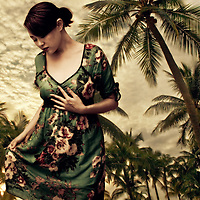 A young asian woman wearing a green floral dress with palm trees in the background looking down with sad emotion