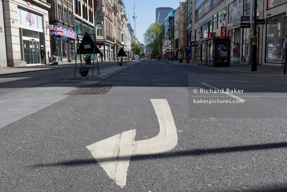 At the beginning of the fourth week of the UK government's lockdown during the Coronavirus pandemic, and with 120,067 UK reported cases with 16,060 deaths, a traffic arrow points right on Oxford Street that would normally be a busy thoroughfare for shoppers and traffic and which remains largely deserted at mid-day, on 20th April 2020, in London, England.