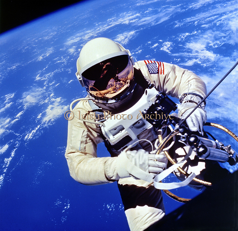 US Astronaut Edward H White II carrying out external tasks during third orbit of Gemini-Titan 4 flight.  NASA photograph.