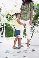 Girl (5-6 years) hugging mothers leg standing on verandah