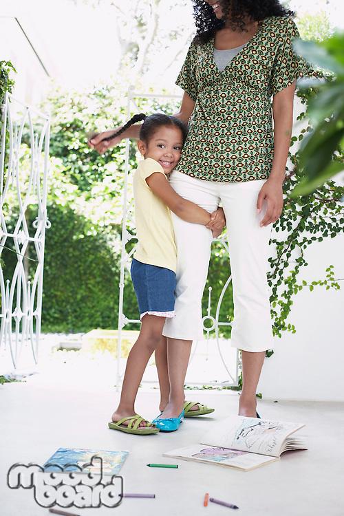 Girl (5-6 years) hugging mothers leg standing on verandah