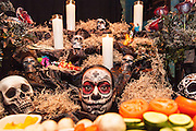 Performer sits under the vegetable table at the IAS Voodoo Magic Bash at the House of Blues
