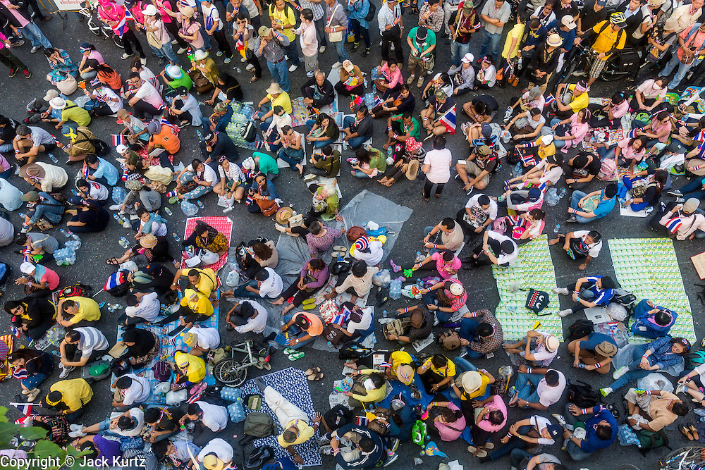 """09 DECEMBER 2013 - BANGKOK, THAILAND: Residents of Bangkok gather on Phitsanulok Road near Government House in Bangkok after the government of Prime Minister Yingluck Shinawatra collapsed Monday. Thai Prime Minister Yingluck Shinawatra announced she would dissolve the lower house of the Parliament and call new elections in the face of ongoing anti-government protests in Bangkok. Hundreds of thousands of people flocked to Government House, the office of the Prime Minister, Monday to celebrate the collapse of the government after Yingluck made her announcement. Former Deputy Prime Minister Suthep Thaugsuban, the organizer of the protests, said the protests would continue until the """"Thaksin influence is uprooted from Thailand."""" There were no reports of violence in the protests Monday.      PHOTO BY JACK KURTZ"""