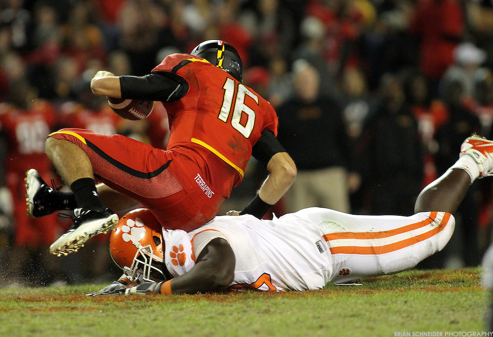 October 15, 2011; College Park, MD, USA; Maryland Terrapins quarterback C.J. Brown (16) avoids a sack by falling on Clemson Tigers defensive tackle Brandon Thompson (98) during the first half at Byrd Stadium. Brian Schneider-www.ebrianschneider.com
