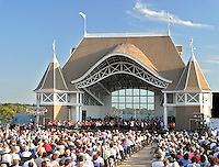 Crowd enjoying a summer concert outdoors at the Lake Harriet Bandstand in Minneapolis, Minnesota.
