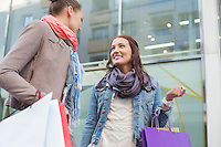 Low angle view of female friends with shopping bags looking at each other against store