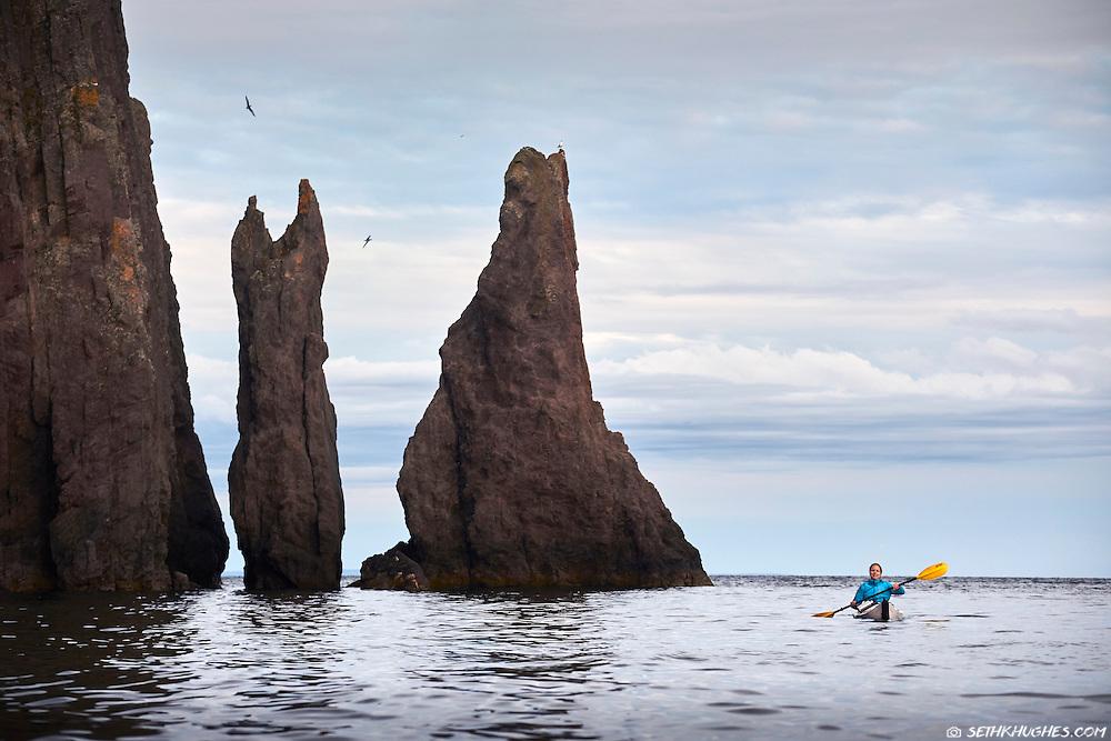 A woman sea kayking in Trinity Bay, Newfoundland, Canada