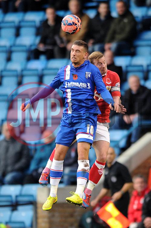 Bristol City's Wade Elliott jumps up with Gillingham's Cody McDonald for the header - Photo mandatory by-line: Dougie Allward/JMP - Mobile: 07966 386802 - 08/11/2014 - SPORT - Football - Gillingham - Priestfield Stadium - Gillingham v Bristol City - FA Cup - Round One