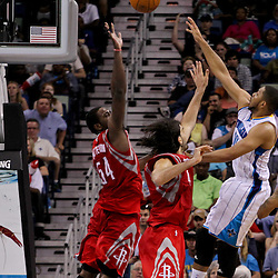 April 19, 2012; New Orleans, LA, USA; New Orleans Hornets shooting guard Eric Gordon (10) shoots over Houston Rockets shooting guard Courtney Lee (5), forward Luis Scola (4) and power forward Patrick Patterson (54) during the second half at the New Orleans Arena. The Hornets defeated the Rockets 105-99.   Mandatory Credit: Derick E. Hingle-US PRESSWIRE