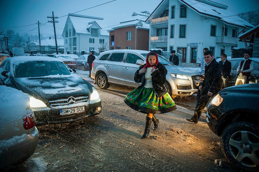 A woman in traditional dress crosses a street in the snow heading to the community centre where a wedding is taking place.