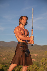 hot tan man muscular man with long brown hair in a kilt holding a sword on a mountain side