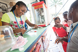 "6 December 2017, Abidjan, Côte d'Ivoire: Zainab (left) from Côte d'Ivoire takes orders, as a food truck, named ""Bon Appetit"" parked near the Global Village provides food to participants in ICASA 2017. The 19th International Conference on AIDS and STIs in Africa (ICASA) 2017 gathers thousands of researchers, medical professionals, academics, activists and faith-based organizations from all over the world, all looking to overcome the HIV epidemic and eliminate AIDS as a public health threat."