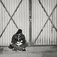 Man sitting by doors of corrugated iron on Bryggen in central Bergen reading a book and listening to music in early spring