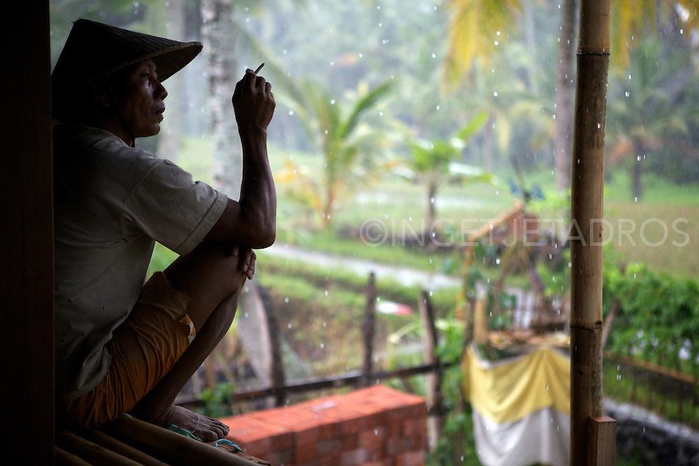 A Balinese worker taking a break during a heavy rainfull. &copy;Ingetje Tadros<br /> www.ingetjetadros.com