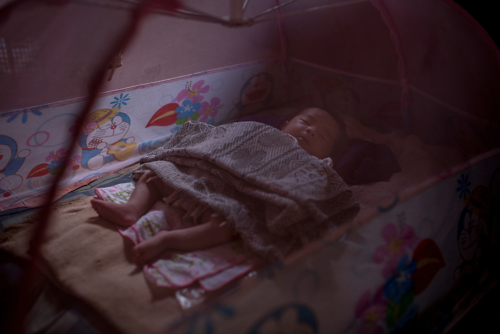 A 15 day old baby in the village of Khoc Kham. The village is not connected to the main electrical grid and many residents operate their own turbines to power lights and sometimes small appliances.