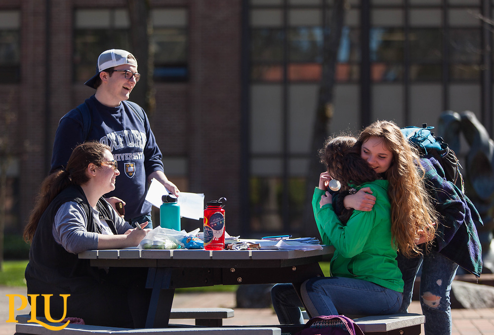 Students spread out their work on a table of Red Square in the spring sunshine at PLU, Monday, April 3, 2017. (Photo: John Froschauer/PLU)