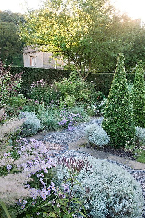 The Pink Garden in late summer with pebble mosaic paving by Maggie Howarth, Buxus sempervirens (box) topiary, Santolina chamaecyparissus, Aster amellus 'Rosa Erfullung', Helictotrichon sempervirens and Calamagrostis brachytricha at Gresgarth Hall & Gardens, Lancashire, England