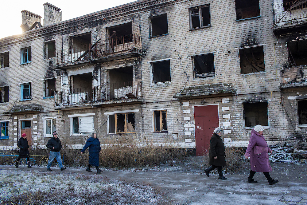 Local residents walk past a destroyed building to receive free bread delivered by the Good Word Protestant Church in need on Thursday, December 10, 2015 in Mariinka, Ukraine.