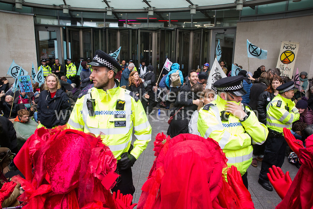 London, UK. 11 October, 2019. The Red Brigade joins climate activists from Extinction Rebellion blocking the main entrance to the BBC's New Broadcasting House on the fifth day of International Rebellion protests. They were demanding that the broadcaster 'tell the truth' regarding the climate emergency.