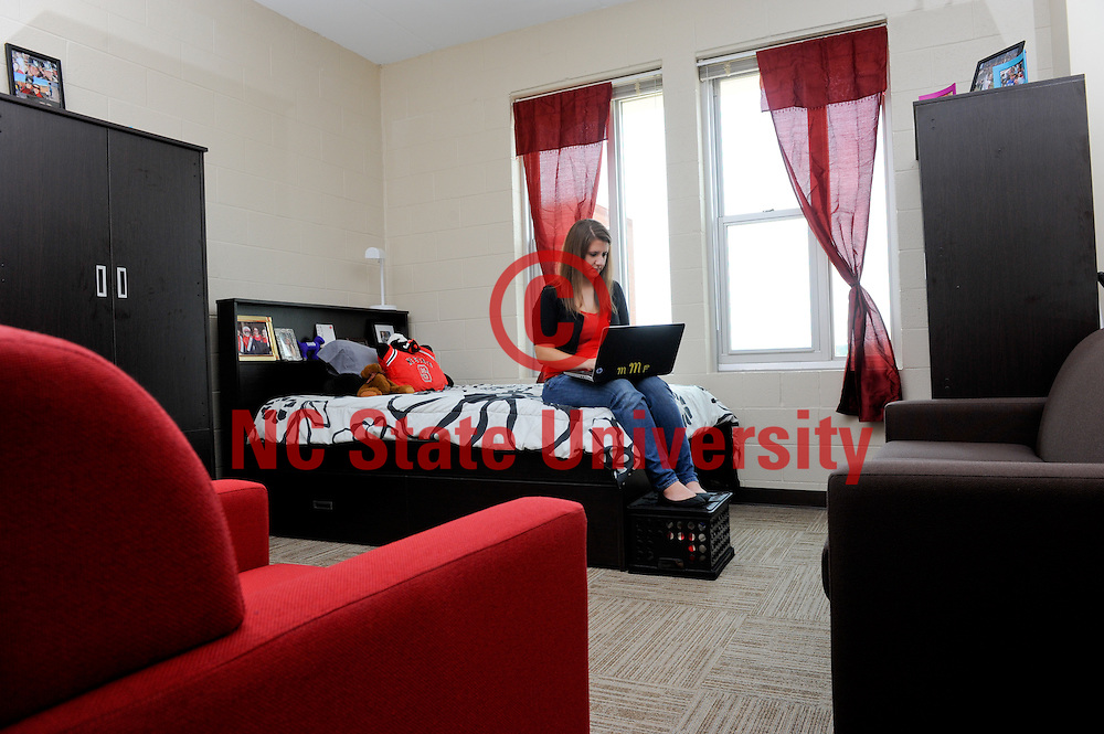 A student uses her dorm room in the newly opened Wolf Ridge on Centennial Campus. Photo by Marc Hall