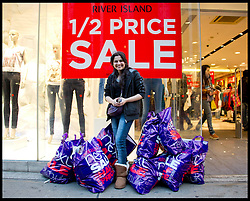 Hiral Fadadu with her pile of bargains on a busy Oxford Street in Central London as bargain hunters shop in the  Boxing Day Sales, Monday December 26, 2011. Photo By Andrew Parsons/i-Images
