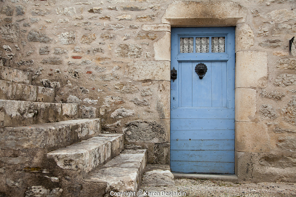 A blue door stands out against a stone wall and steps in the village of Bouzies along the Lot River in southwestern France.