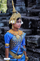 Khmer Beauty: A beautiful young lady dancer is dressed in the traditional Khmer fashion wait her cue amongst the ruins of Bayon Angkor Thom, Siem Reap Cambodia.
