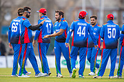 Afghan captain Gulbadin Naib (centre) is congratulated by his team mates after he bowls out Scotland captain Kyle Coetzer for 79 runs during the One Day International match between Scotland and Afghanistan at The Grange Cricket Club, Edinburgh, Scotland on 10 May 2019.