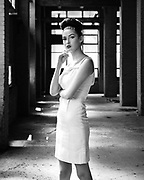 Black and white fashion photo of 1950s model in abandoned building