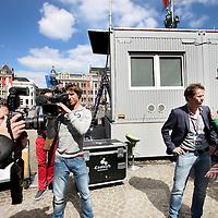 Nederland, Amsterdam , 28 april 2013.<br /> Voorbereidingen en opbouw van de media op de Dam Koningsdag 30 april.<br /> De NOS heeft een glazen huis op de Dam geinstalleerd van waaruit verslag zal worden gedaan tijdens de Kroningsdag.<br /> De nodige voorbereidingen worden getroffen. Kabels worden aangebracht, perstribunes opgebouwd etc.<br /> Op de foto: NOS Nieuwslezeres Astrid Kersseboom en een regisseur van het NOS journaal bij het glazen huis op de Dam omringd door de pers.<br /> Preparation and build up the media at the Dam in Amsterdam for King's Day, April 30th.<br /> The NOS installed a glass house at the Dam from which they will be broadcast at the King's Day.<br /> Foto:Jean-Pierre Jans