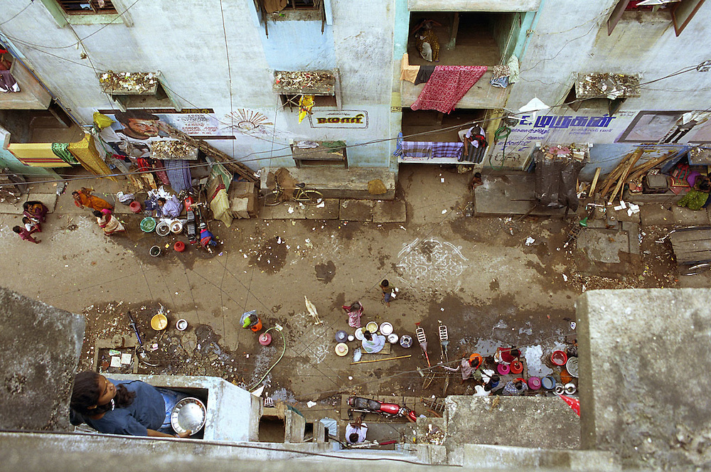 India. Tamil Nadu. Chennai (Madras). December, 2001. A view from the 3rd floor of one of the state built Housing Board apartment blocks inside the Walltax Road slum. This slum houses 240 Dalit families. Each apartment is the same size with two very small rooms, a half size room for a kitchen and one latrine. An average of four to seven people lives in each apartment. There is no running water; a state water tanker (truck) comes every day to give residents a free supply.  Some apartment blocks have no electricity either; however, residents find non-official ways to bring electricity into their homes. The average income in the slum is $2 a day, most men work as lorry drivers, auto rickshaw drivers, goods carriers and sanitation workers. With only two state employees to take care of sanitation, the situation in this sprawling slum is very poor. Many residents feel that the government authorities simply don't care about their living conditions.